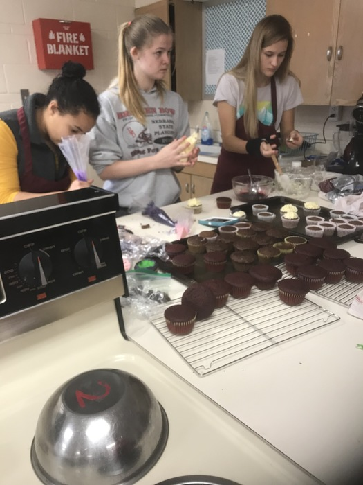 Students frosting cupcakes
