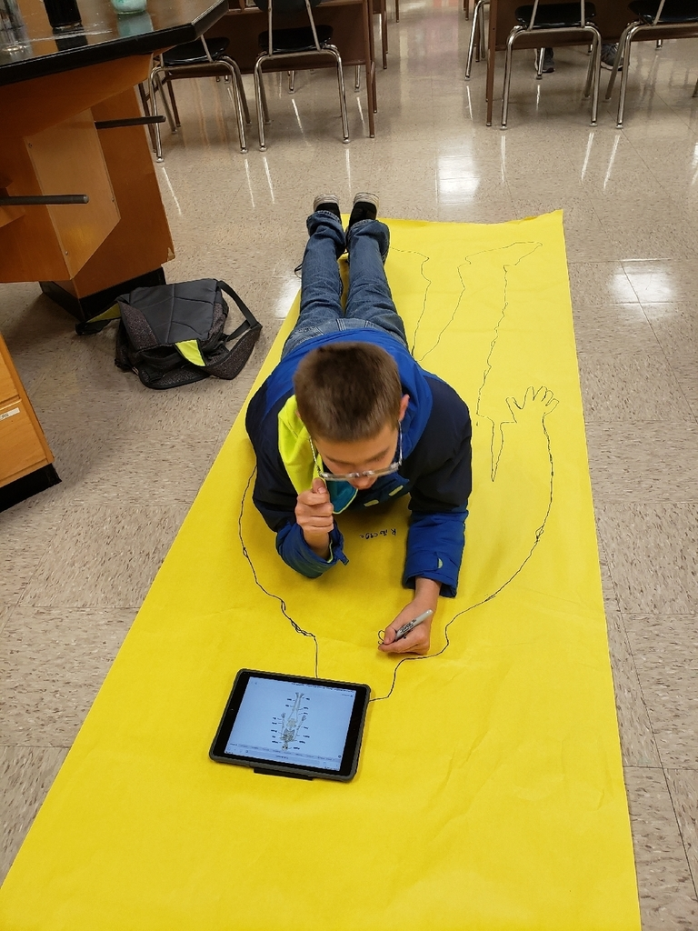 Using his ipad to research the bones in his body.